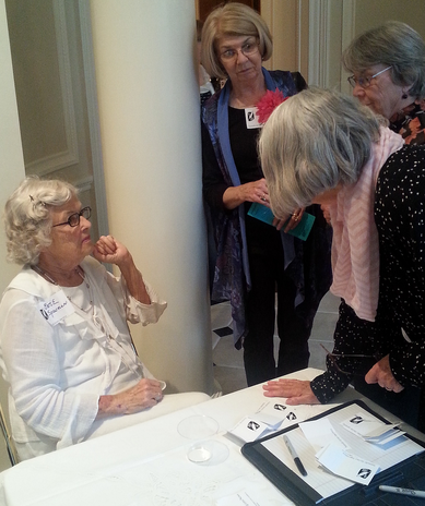 Evie Spearman greets members at sign-in table at the HLA Wine and Cheese Party held at Les Forgerons, the home of Mrs. Mark Smith of Huntsville.