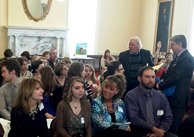 AWF staffer Danny Gamble (standing center) talks AHSLAA with audience members.
