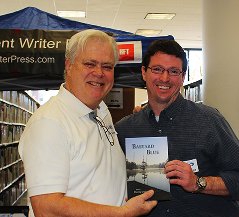 """Murray Shows Steve a copy of his first book, """"Bastard Blue"""" published by Press53."""